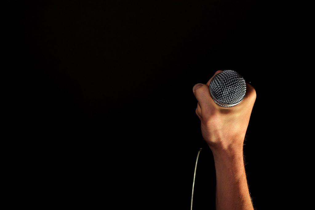 Käsi pitelee mikrofonia ylhäällä mustaa taustaa vasten