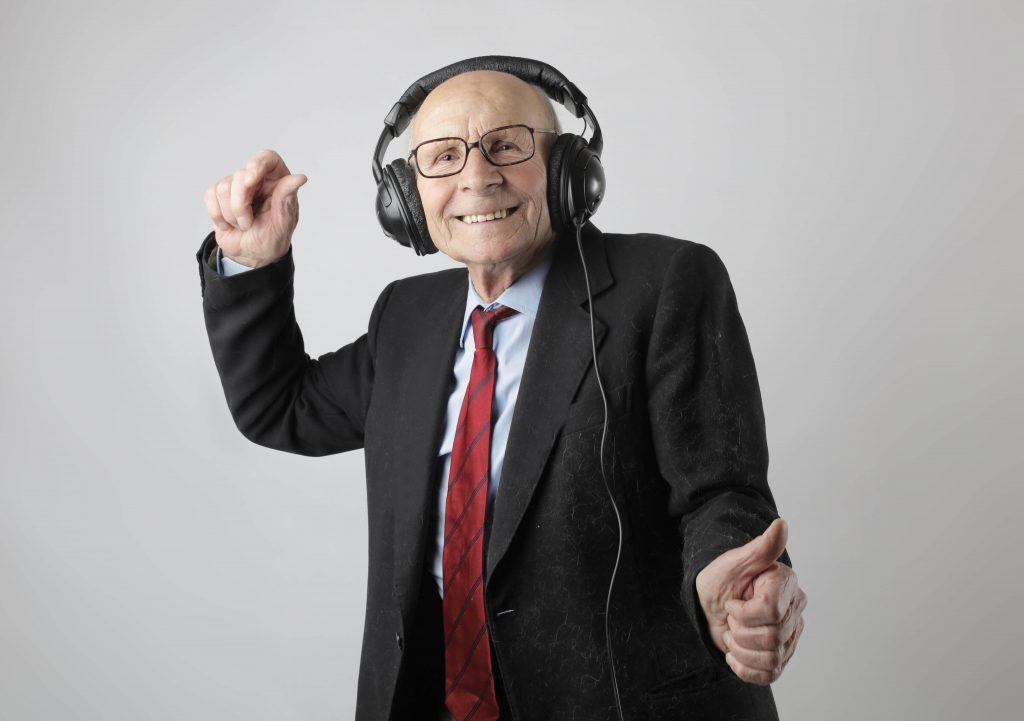 Vanhemmalla herrasmiehellä on päällään puku ja kravaatti. Hän kuuntelee musiikkia isoilla mustilla kuulokkeilla ja tanssii.