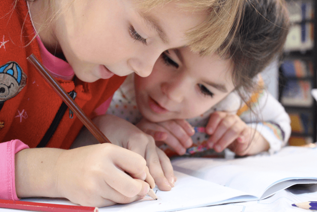 Kaksi lasta täyttää yhdessä harjoitusvihkoon koulutehtäviä.