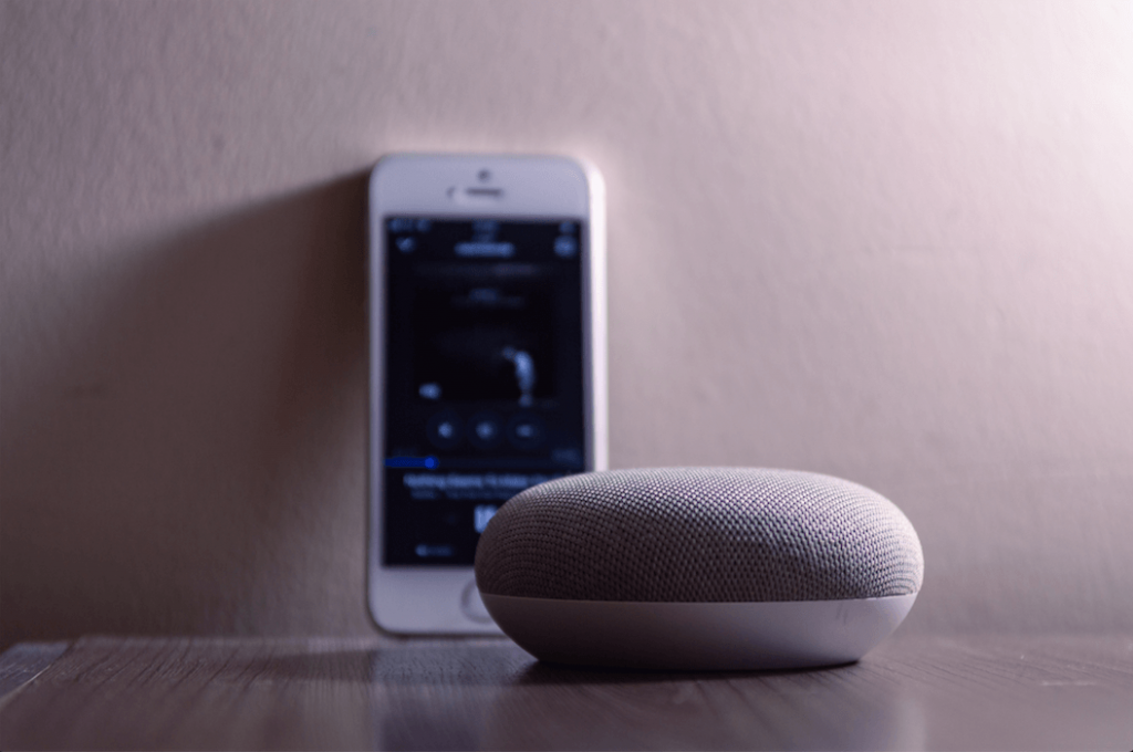 Smart speakers are used to play audio content for longer durations. A smartphone and smart speaker.
