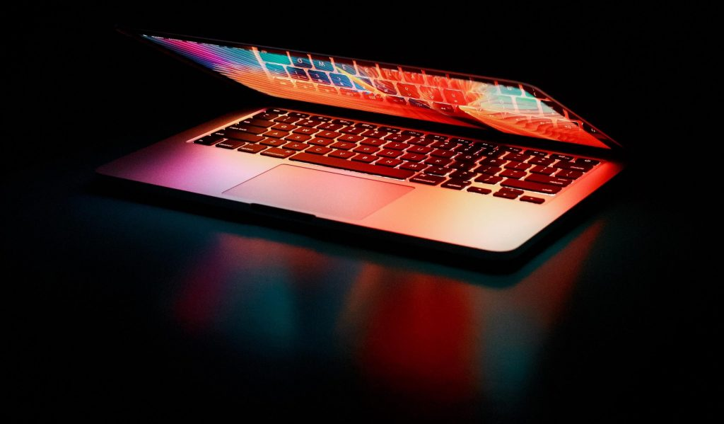 Miksi ääniominaisuus voi mullistaa verkkosisältöjen käyttökokemuksen? Pöydällä on upeissa väreissä hohtava läppäri, muuten tausta on musta.