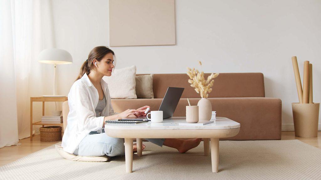 Miksi ääni pitäisi löytyä verkkosivuilta? Nainen istuu sohvapöydän ääressä ja hänellä on edessään kannettava tietokone.