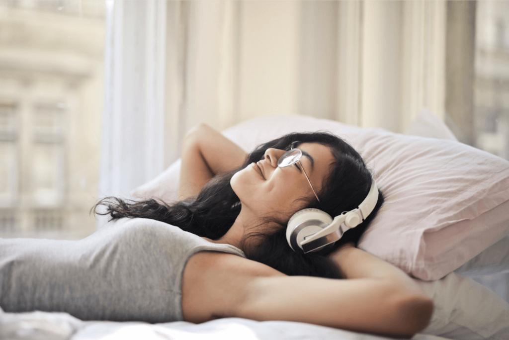 Kontrollipaneeli parantaa verkkosivuja kuuntelevan asiakaskokemusta. Nainen makaa sängyllä isot kuulokkeet päässään, silmät suljettuina ja hymyilee leveästi.