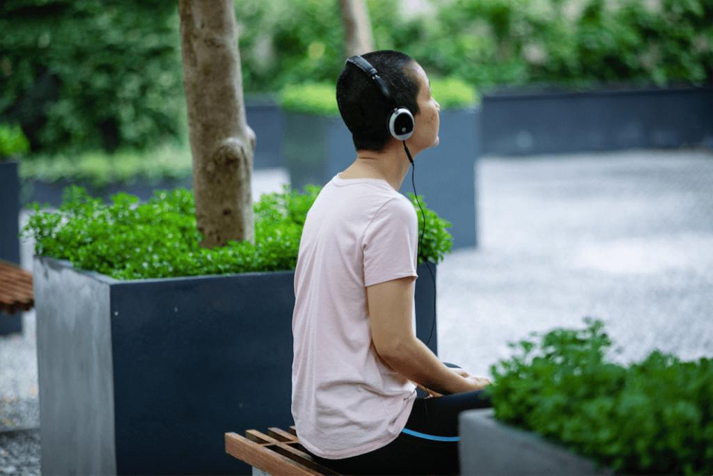 Neuraaliääni. Nainen istuu penkillä ja hänellä on mustat kuulokkeet korvillaan. Ympärillä näkyy suuriin harmaisiin istutuslaatikoihin istutettuja kasveja.