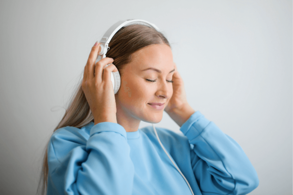 Listenable website. A woman is wearing large headphones and listening to audio contet.