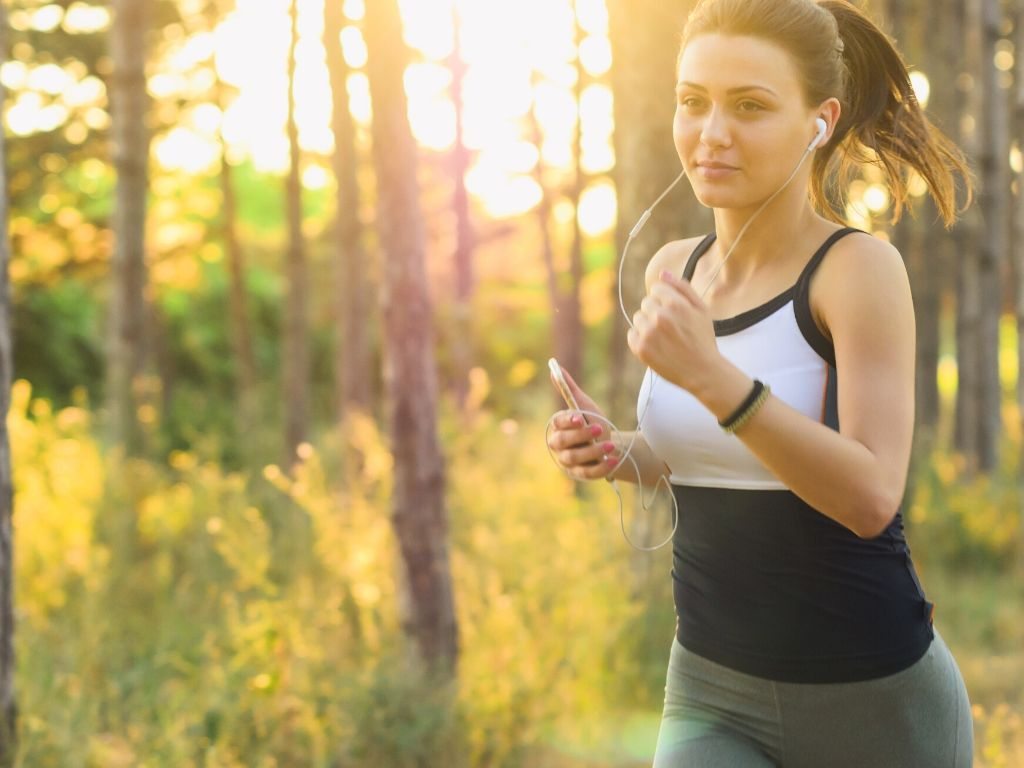 Branding and voice. A woman is jogging and she has headphones on and a mobile phone on her hand. She is listening to audio.
