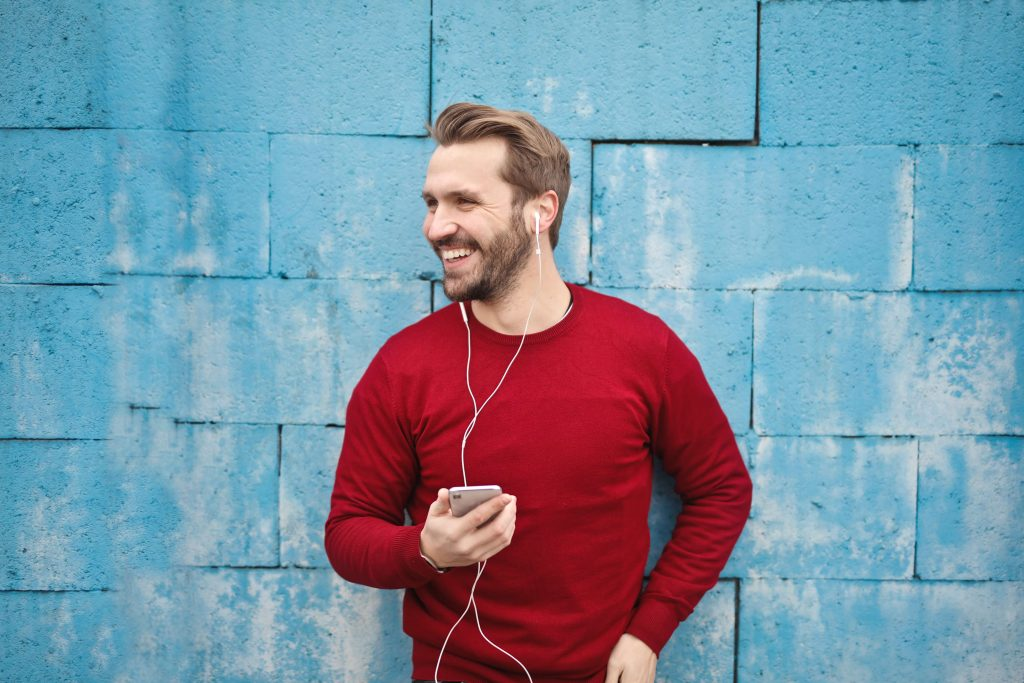 A man is listening to audio contents with headphones. He has a mobile phone on his hand. The background is turquoise and he is wearing a red shirt.